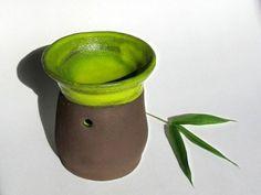 Diese Vasenserie der Keramikerin Saskia Lauth besteht aus Röhrenvasen in verschiedenen Höhen. Von Hand in dunkelbraunem Ton geformt und mit einer gelbgrünen Glasur im Inneren und am oberen Rand versehen, erinnern diese schlanken Vasen an Bambushalme.