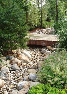 A former neighbor made a  dry creek bed through her front yard, under a wooden fence and through her back yard. It was functional and added a distinctive look to her yard.