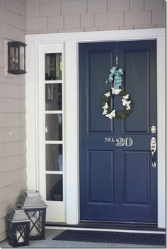 Navy front door, painted number, seasonal wreath, lanterns