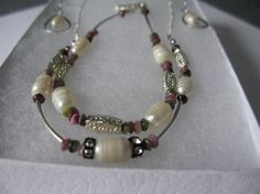 Multi tourmaline and freshwater cultured pearls combine in this lovely wedding set perfect for bride or mother of the bride. Necklace is choker style being partly made with silver plated chain. The matching bracelet and necklace both have matching toggle clasps. Earrings are made with square silver wire bent in a teardrop shape with a freshwater pearl dangling inside it. Earrings are approximately 1.5 inches long. Bracelet will fit a 7.5 inch wrist. The necklace is approximately 10 inches…