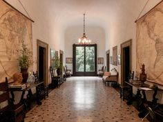 T Magazine / Villa Albergoni / Italian Villa / Set decoration / Interior design / Grand entrance hall / Foyer decor / Entry decor / Old world charm / Traditional gallery furniture placement / Large hanging maps as decor / Terrazzo floors