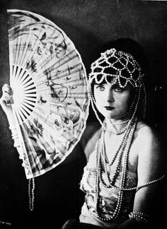 In that era women used to wear heavy headgears made with pearls and feathers. The main accesory was the fan which was use for communication with people.