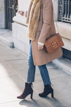 Jess Ann Kirby styles neutrals in a camel coat, faux fur scarf, raw hem jeans and velvet ankle booties