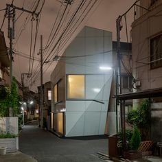 wiel arets architects wraps A' house in tokyo with dual skin. nestled within the dense residential streets of tokyo, this compact dwelling consists of five horizontally divided spaces, each connected with a narrow winding staircase.