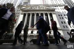 Pedestrians walk by the New York Stock Exchange: Pedestrians walk by the New York Stock Exchange near Wall Street in New York City on…
