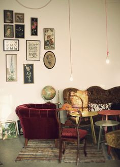 Old timey red chair and pictures grouped to shape- the dangling bulbs, too!