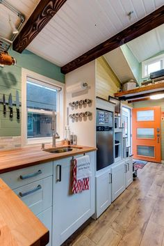The Wanderlust is a 170-sq-ft tiny house on wheels, currently traveling the U.S. Its owners purchased the 20' x 8.5' home from Tumbleweed Tiny House Co. as a barn raiser home. | Tiny Homes