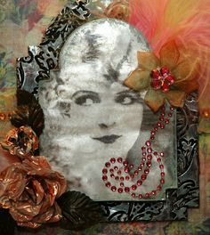 """This frame was made for a  """"bling"""" challenge.  It is Tim Holtz' large and smaller Vintage Cabinet card Sizzix die, cut out of chipboard, covered with embossed metal foil that has been distressed. The photograph is a transfer onto the metal foil using Matte Multi Medium as the transfer agent. I added the feathers, flowers, ribbon and bling after putting it all together."""