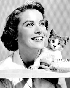 Grace Kelly in 1948, photographed clutching a kitten while working as a part-time model.