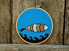 Citrus Sardine is an original mixed media artwork, screen printed and hand embroidered.  Screen printed in black on blue linen and embroidered with