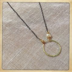 This wonderful necklace by Alabama artist Kristen Hughes is the kind of jewelry that becomes second skin—you're not going to want to take it off. A single gold circle is held by antiqued silver chains and adorned by a perfect tiny pearl. $45.00 Available online at http://shopblueskies.net/