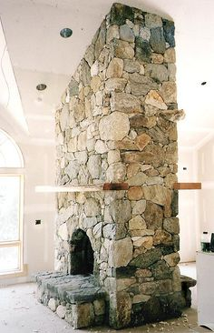 Double-sided stone fireplace - I want to find a house with one of these, would be perfect if the other side was in the kitchen.