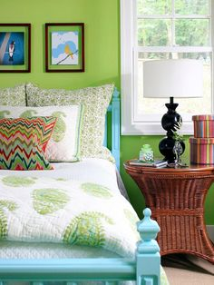 Lime green walls & painted sky blue bed frame creates fresh vibe. Large-scale paisley quilt, wicker table & whimsical bird prints complete the look
