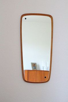 A funky shaped wall mirror from the 1960s to 70s. Made from solid teak wood it is very much the Gplan / Danish style and looks fantastic hung.