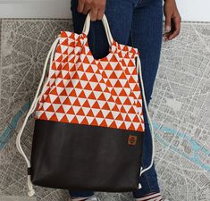 Comfortable and practical drawstring backpack! Easy to open and close, it can be carried as a backpack or on one shoulder only. Perfect for any occasion: urban, outdoors, school, you name it! To make it, I used : - dark brown leatherette - orange triangle cotton fabric - gray Diy Backpack, Drawstring Backpack, Drawing Bag, Orange Backpacks, Backpack Pattern, Orange Bag, Leather Bags Handmade, Fabric Bags, Fashion Bags