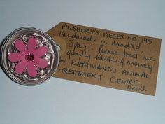 Pillsbury's Pieces No, 195. Pin with pale pink metallic capsule with bright pink flower. In exchange for a donation to KATHMANDU ANIMAL TREATMENT CENTRE, Nepal. Available at St. George's Church, Madrid on Saturday 13 June from 11.00 - 15.00.