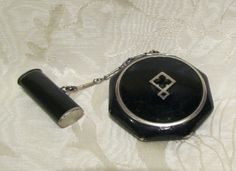 This is a wonderful 1930's Art Deco black enamel and silver tone octagon shaped tango powder, rouge, mirror and lipstick compact. The piece is in good condition