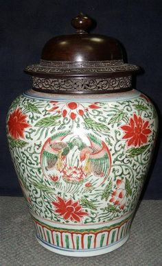 A famille verte jar with wood cover, period of Kangxi, the sides painted with four roundels of pairs of birds on a ground of scrolling lotus, the rim now mounted in copper, a lappet band on the foot, the jar 26.5cm (10.5 in.) high (2)