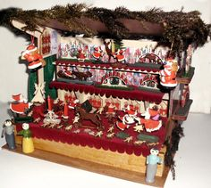 A German market stall for dollhouse with many vintage handcrafted figures. There are elves and Santas, candlesticks and candle arches, a horse on wheels, and more. The stall is 24 x 20 x 18 cm tall.