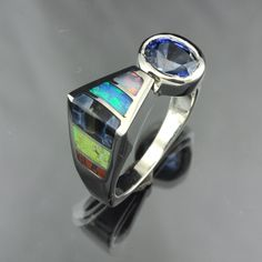 Ring |  Jeweler Jim on Etsy.  White Gold Ceylon Sapphire and inlaid with two colors of Australian Opal, Pietersite, Gaspeite, and a small piece of Dinosaur bone