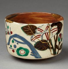 japaneseaesthetics:    Tea bowl, reddish brown stoneware, with a marbled glaze, and floral decoration in colours on a cream-coloured patch. It has been mended with gilt lacquer. 18th century, Japan. V Museum