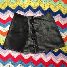 "90s Black Faux Leather Button Front Skirt • Excellent condition-- like new!! • Can be worn high-waisted • Skater skirt style, not fitted • Waist is about 28"" • Vegan leather • Only flaw is teeny tiny pinprick where the tag was on the waist-- not noticeable at all Vintage Skirts"