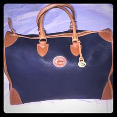 "Authentic Dooney & Bourke Large Carry On Satchel. Weekend Wear HostPick  Authentic Classic Dooney & Bourke Navy with Tan pebbled leather. It's actually a carry on. I used it as a purse and briefcase   Excellent condition! Special ordered from Nordstrom. 16"" W. 12"" D  5 big fluffy towels fit in it! This bag is huge! I will do a not for sale listing to show bottom. It has small Brass legs. Will throw in matching Planner shown in separate listing..Bag was $695 and planner was $250. No Trades No…"
