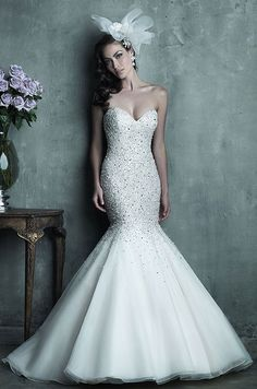 The beading on this strapless English net and organza mermaid gown is perfect, covering the sweetheart bodice and gradually sprinkling the skirt with tiny sparkling gems. Allure Couture, 2014