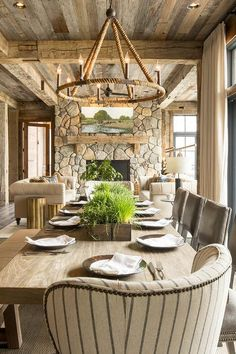 Country dining room feels richer by using a mix of textures and colors such as a long wood dining table and nailhead trim chairs under a rope candelabra chandelier.