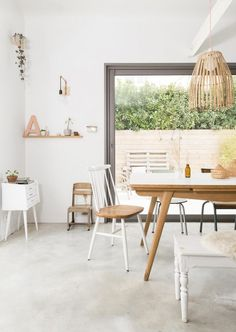Concrete, wood and rattan in the simple dining space of a charming and relaxed Biarritz home. Julien Fernandez.