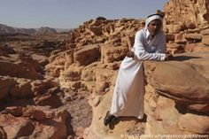 A Bedouin guide in traditional costume stands in the Coloured Canyon in the Sinai Desert, Egypt. Photo by Stuart Forster.
