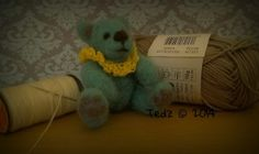 Needle felted miniature teddy bear.  Cynthia is 6cm.  She is made from a beautiful turquoise shade of pure unspun wool, and adorns a crocheted neck piece (which is permanently attached).  She also has grey paw pads and inner ears, and her nose and eyes are also needle felted.