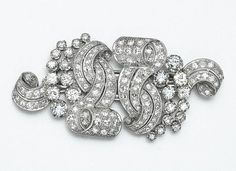 DIAMOND DOUBLE-CLIP/BROOCH, CIRCA 1935 The fanciful scroll motifs set with 142 old European-cut and single-cut diamonds weighing approximately 7.00 carats, mounted in platinum.