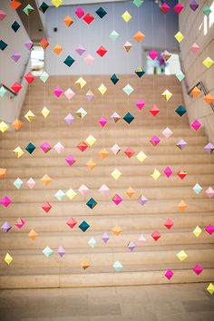 Dozens of origami shapes hanging from ceiling... especially effective on a staircase.  Saw something similar at dept. store using different textured white butterflies... created ethereal feel while rising on escalator.
