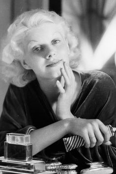 8th July 1932: Jean Harlow applying make-up to her face in her dressing room. One of her famous superstitions was to not leave her dressing room without first looking at her 'lucky mirror', photographed by Clarence Sinclair Bull.