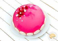 Entremet composé d'un financier agrémenté de framboises, d'un insert gélifié à la framboise et d'une mousse au lait d'amandes recouvert d'un glaçage rose.