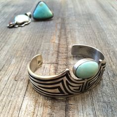 Here we have a beautiful sterling silver overlay cuff with Dry Creek turquoise by renowned Navajo artist Charles Johnson. What a gorgeous contemporary design! And on top of that, the pale blue-green Dry Creek turquoise--which comes from a small mine in Lander County, Nevada-and is also referred to as Sacred Buffalo turquoise. See Photo 3 to view how elegant the bracelet looks on the wrist, and Photo 5 to compare size with a few other bracelets in the shop.  Johnson began making jewelry at a…
