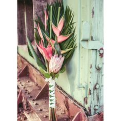 Tall heliconias and palm leaves make a modern wand-style bouquet. Tuck in a pink protea and wind around white ribbon and you've got something beautiful