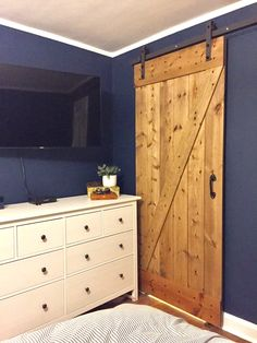 """Dark blue and white bedroom, """"Gentlemans Gray"""" by Benjamin Moore. White Hemnes dresser from IKEA, Barn Door kit from Overstock and floor with 50/50 weathered oak and special walnut stain. Design by Beam&Bloom."""