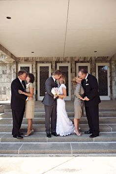 parents kissing with bride and groom photo