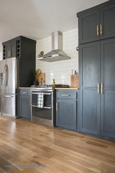 DIY Kitchen Cabinets, Fridge Enclosure and Pantry.  Love the dark gray almost black cabinets with brass hardware