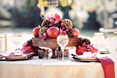 A wooden vessel overflowing with pine cones and pomegranates.