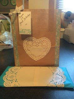 Brown paper bag decorated with flowery washi tape and a heart shaped doily