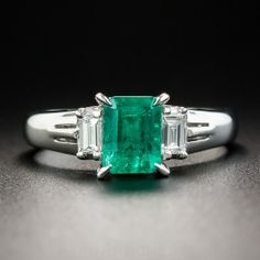 A gorgeous vibrant green Colombian emerald, weighing 1.12 carats, radiates between a pair of bright white baguette diamonds in this sleekly tailored and timeless estate jewel crafted in platinum. Classic. Currently ring size 6.