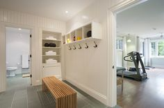 Home workout room changing area features vertical shiplap walls fitted with built-in shelving situated across from a wood slatted waterfall bench atop slate tiled floors facing wall-mount cubbies over iron wall hooks.