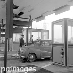 An Austin Somerset car draws up at one of the new toll gate booths near the mouth of the new Thames Tunnel at Dartford, Kent. The tunnel runs between Dartford and Thurrock, Essex. 13th November 1963