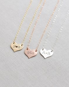 Small Engraved Heart Necklace by Olive Yew. This dainty small heart necklace can be personalized with sweetheart initials, a name or left blank. The petite heart charm measures 1/2 in diameter and hangs from a 17 inch chain. Available in silver, gold or rose gold.