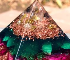 A delicate orgonite pyramid to open and heal the Heart Chakra. This little pyramid has a powerful energy radiating from its' core, intended to purify energy around the heart so you may open to love.