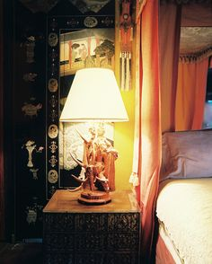 Tony Duquette - A silk canopy bed paired with antique screens and an ornate nightstand