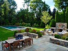 terrasse en dalles cosy aménagée avec une cheminée en pierre naturelle, un salon de jardin en osier et en bois et une piscine enterrée